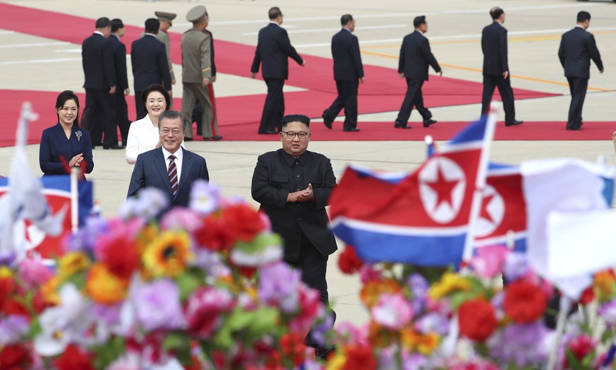 South Korean President Moon Jae-in, front left, walks with North Korean leader Kim Jong Un, front right, upon Moon's arrival at Sunan International Airport in Pyongyang in North Korea, Tuesday, Sept. 18, 2018. Moon arrived in North Korea on Tuesday for his third and possibly most challenging summit yet with Kim  in which he hopes to break an impasse in talks with the United States over the North's denuclearization and breathe energy into his own efforts to expand and improve relations between the Koreas. (Pyongyang Press Corps Pool via AP)