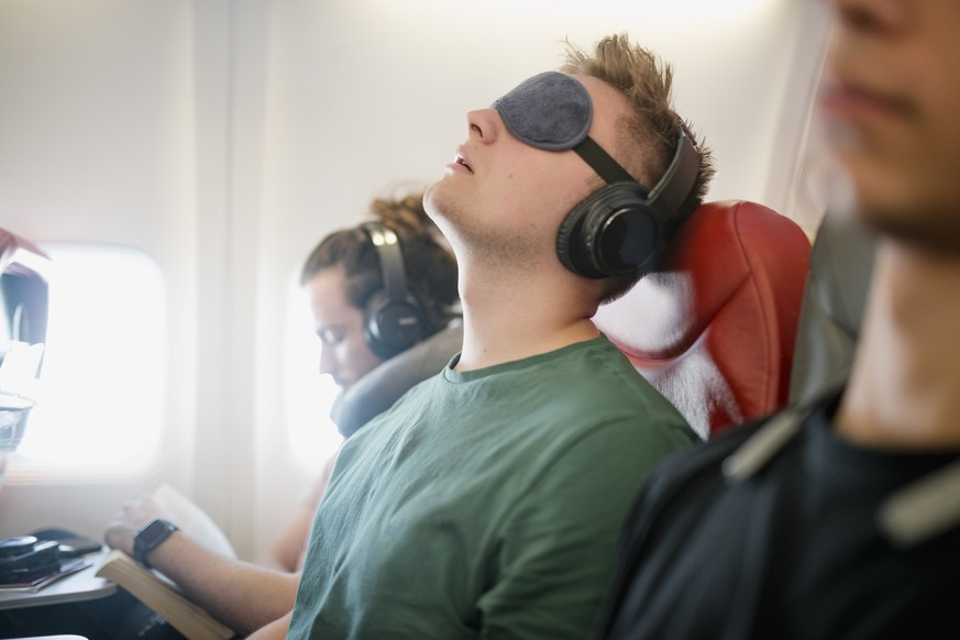 Close up shot of a young man asleep with his head back snoring on a flight in economy class. He is wearing wireless headphones and has an eye mask on.