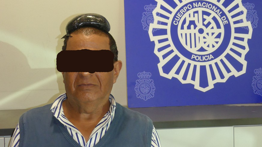 A man poses with a drug package on his head, that he hid under a toupee, after being arrested in Barcelona, Spain, in this picture released on July 16, 2019. Spanish National Police via REUTERS ATTENTION EDITORS - THIS IMAGE HAS BEEN SUPPLIED BY A THIRD PARTY. NO RESALES. NO ARCHIVE. FACE OBSCURED AT SOURCE