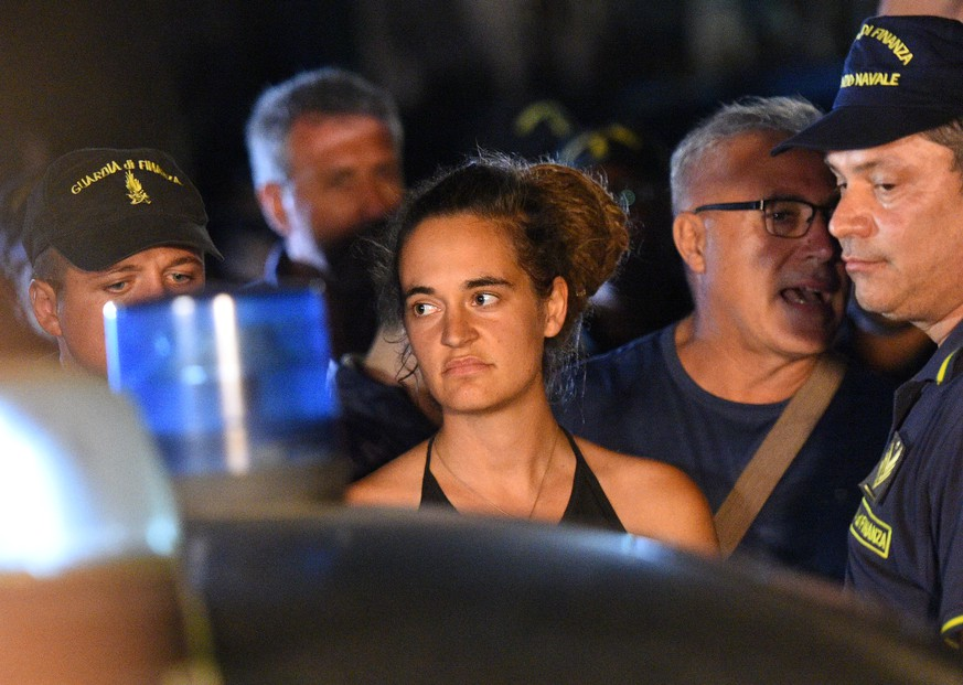 Carola Rackete, the 31-year-old Sea-Watch 3 captain, is escorted off the ship by police and taken away for questioning, in Lampedusa, Italy June 29, 2019. REUTERS/Guglielmo Mangiapane