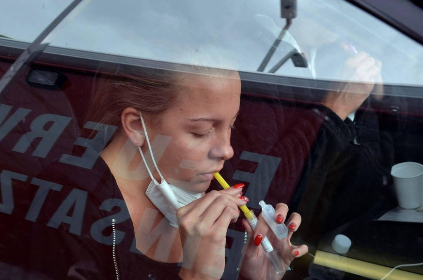 A young woman makes a gargle test from her car to detect the Covid-19 in the test lane set up next to the Ernst Happel soccer stadium in Vienna Austria, 09 October 2020. Citizens can come with their registration certificate and their health card and have access to a PCR test that has been developed in Austria and consists of gargling with a liquid for half a minute, then spiting out and afterwards just waiting to be informed if the virus is traced. The test is free of charge for those registered in Vienna and in one of these situations: having returned from a country considered safe by the Austrian government, having spent more than four days in another Austrian region or having been in contact with positives. Self-service PCR test in PUBLICATIONxINxGERxSUIxAUTxONLY Copyright: xJorgexDastisx GRAF7478 20201009-637378408242829107