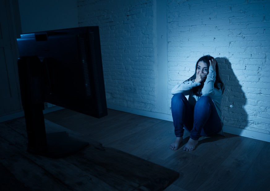 Dramatic portrait of sad scared young woman sitting on the ground staring a computer suffering bullying and harassment. Being online abused by stalker feeling desperate in Internet problem concept.