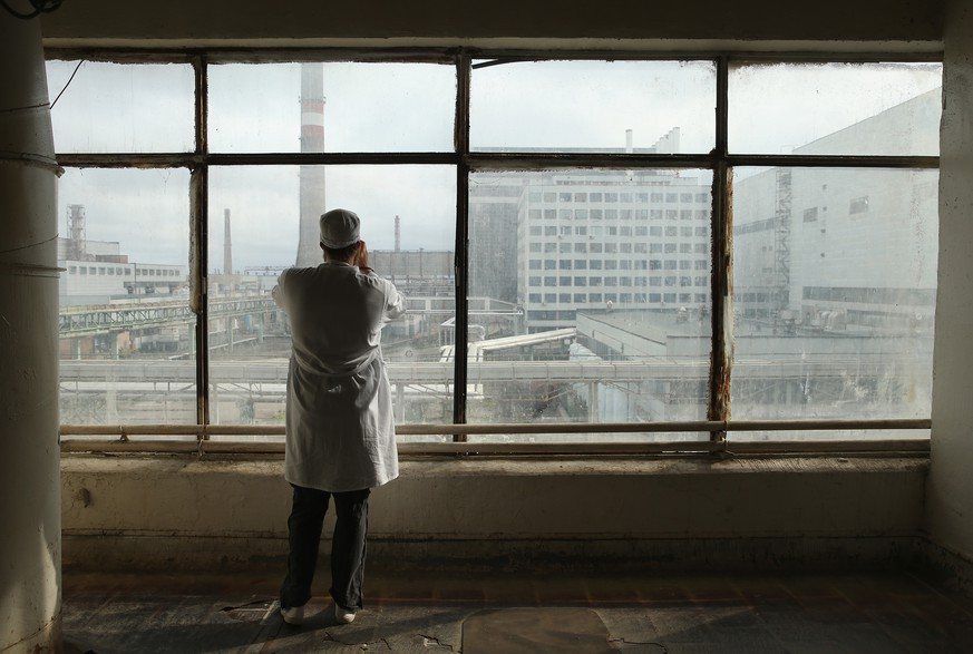 CHORNOBYL, UKRAINE - SEPTEMBER 29:  A visitor touring the former Chernobyl nuclear power plant takes a photo through a window looking towards facilities that house reactors one and two on September 29, 2015 near Chornobyl, Ukraine. The Chernobyl plant is currently undergoing a decades-long decommissioning process of reactors one, two and three, which continued operation for years following the accident at reactor four. On April 26, 1986, technicians at Chernobyl conducting a test inadvertently caused reactor number four, which contained over 200 tons of uranium, to explode, flipping the 1,200 ton lid of the reactor into the air and sending plumes of highly radioactive particles and debris into the atmosphere in a deadly cloud that reached as far as western Europe. 32 people, many of them firemen sent to extinguish the blaze, died within days of the accident, and estimates vary from 4,000 to 200,000 deaths since then that can be attributed to illnesses resulting from Chernobyl's radioactive contamination. Today large portions of the inner and outer Chernobyl Exclusion Zone that together cover 2,600 square kilometers remain contaminated. A consortium of western companies is building a movable enclosure called the New Safe Confinement that will cover the reactor remains and its fragile sarcophagus in order to prevent further contamination.  (Photo by Sean Gallup/Getty Images)
