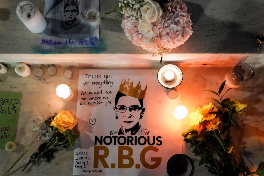 Candles are lit next to pictures of Associate Justice Ruth Bader Ginsburg as people mourn her death at the Supreme Court in Washington, U.S., September 19, 2020.      REUTERS/Joshua Roberts