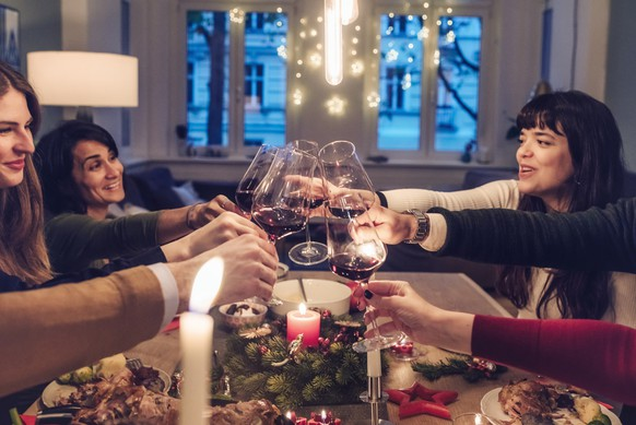 happy young people clinking wine glasses at christmas table