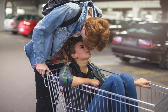 After riding in the shopping cart on the parking lot, a young couple is having a romantic break. The girl is sitting in the cart, and the boy is above her, kissing her gently.