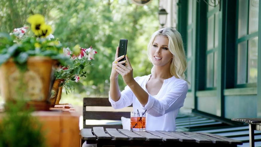 Beautiful young blonde woman in light white shirt relaxing, drinking drinks and taking selfie on smartphone in street summer cafe.