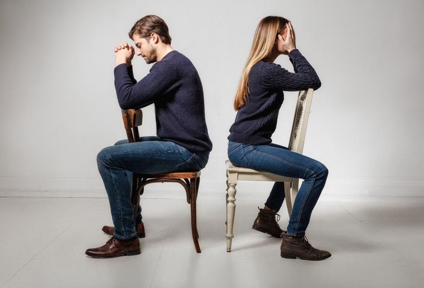 Side view of depressed couple sitting back to back on chairs against gray background
