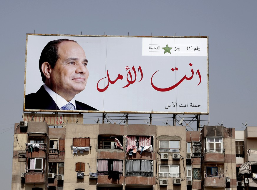 In this Monday, March 19, 2018 photo, an election banner for Egyptian President Abdel-Fattah el-Sissi hangs on top of a residential building with Arabic that reads,