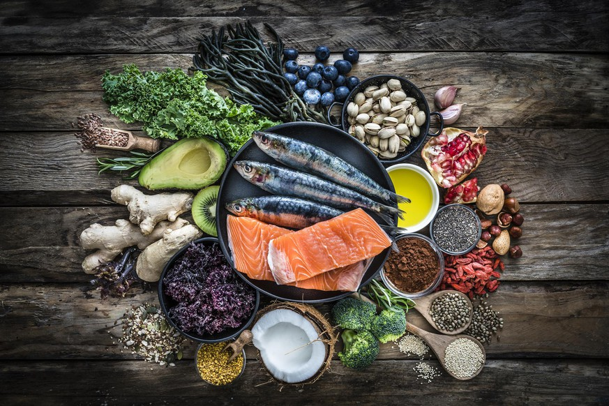 Top view of healthy, antioxidant group of food placed at the center of a rustic wooden table. The composition includes food rich in antioxidants considered as a super-food like avocado, kale, blueberries, chia seeds, coconut, broccoli, different nuts, salmon, sardines, pollen, quinoa, hemp seeds, seaweed, cocoa, olive oil, goji berries, flax seeds, kiwi fruit, pomegranate and ginger. XXXL 42Mp studio photo taken with SONY A7rII and Zeiss Batis 40mm F2.0 CF