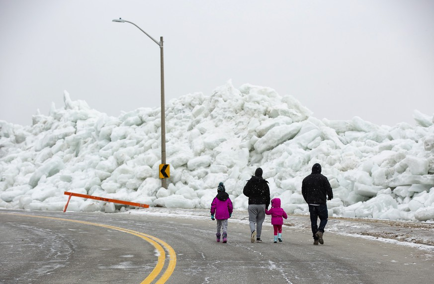 A family walks near a massive build up of ice that was pushed onto the shore of Mather Park in Fort Erie, Ont., Monday, February 25, 2019. A windstorm Sunday broke an ice boom in Lake Erie and allowed the ice, which was floating on the water at the mouth of the Niagara River, to shove over the retaining wall and onto the shore and the roadway above. (Tara Walton/The Canadian Press via AP)