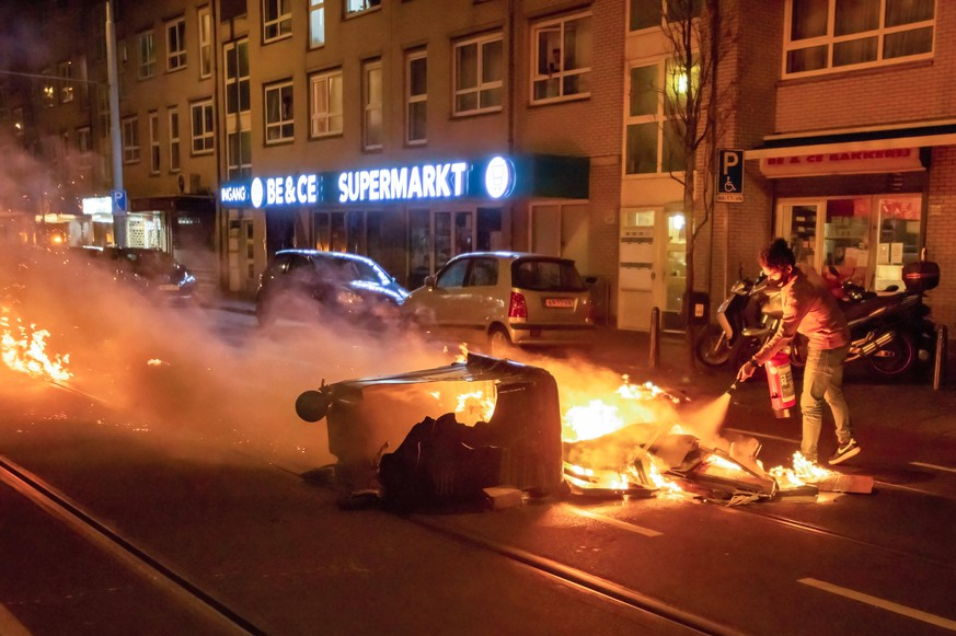 January 25, 2021, The Hague, Netherlands: Local resident attempts to extinguish fire started by the rioters..Riot police and Caine units gathered in mass, prior to the 9 o clock curfew as rioters and protester alike made themselves heard, with the sound of fireworks and the continuous sound of car horns. The curfew in The Netherlands was enforced last Saturday. Some protesters were selling drugs from momentarily parked cars and arrested soon after. The call was made on social media to gather at 20:00 hours, by 20:30 the area was a mass of cars, by 21:00 hours the police had the situation under control. The Hague Netherlands - ZUMAs197 20210125_zaa_s197_110 Copyright: xCharlesxMxVellax