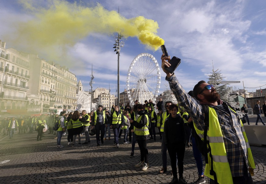 Demonstrators, known as they yellow jackets, protest in Marseille, southern France, Saturday, Dec. 1, 2018, against rising fuel costs and what they claim were dilapidated residential buildings that collapsed Monday Nov. 5, killing eight people.  French authorities on Saturday deployed some thousands of police on Paris' Champs-Elysees avenue to try to contain protests by people angry over rising taxes and President Emmanuel Macron's government. (AP Photo/Claude Paris)
