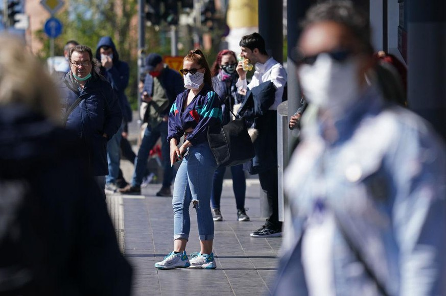 LEIPZIG, GERMANY - APRIL 20: People wearing protective face masks wait for a street tram on the first day face masks became compulsory on public transport in the state of Saxony during the novel coronavirus crisis on April 20, 2020 in Leipzig, Germany. Germany is taking its first steps to ease restrictions on public life that had been imposed weeks ago in order to stem the spread of the coronavirus. Shops across the country are reopening, factory assembly lines are restarting and high schools are holding final exams. Health leaders are monitoring the process carefully for any resurgence of coronavirus infections. The number of infections nationwide is still rising, though so far at a declining rate. (Photo by Sean Gallup/Getty Images)