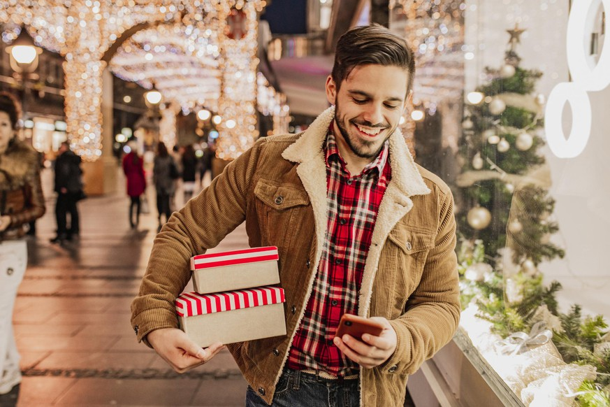 Portrait of a young man holding gift boxes Christmas shopping