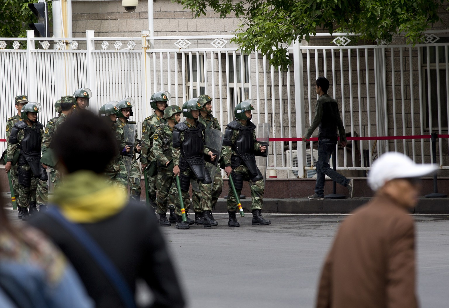 In this May 23, 2014 photo, armed paramilitary policemen patrol on a street in Urumqi, northwest China's Xinjiang Uygur Autonomous Region. So far this month, police in China's restive western region of Xinjiang have broken up 23 terror and religious extremism groups and caught over 200 suspects, state media reported Monday, May 26. (AP Photo/Andy Wong) |