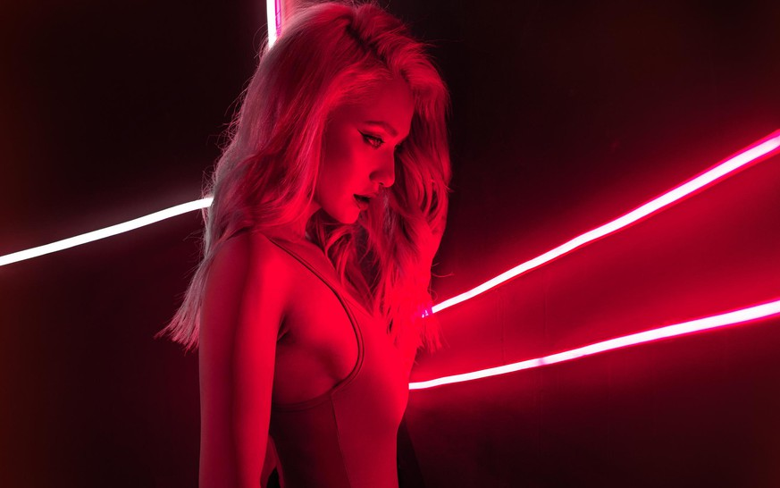 fashion art photo of a girl dressed in red in the night-club. Perfect female body with neon lettering on the background