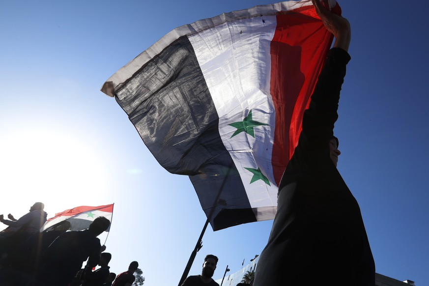 A Syrian government supporter holds up a Syrian national flag as he chants slogans against U.S. President Trump during demonstrations following a wave of U.S., British and French military strikes to punish President Bashar Assad for suspected chemical attack against civilians, in Damascus, Syria, Saturday, April 14, 2018. Hundreds of Syrians are demonstrating in the landmark square in the Syrian capital, waving victory signs and honking their car horns in a show of defiance. (AP Photo/Hassan Ammar)