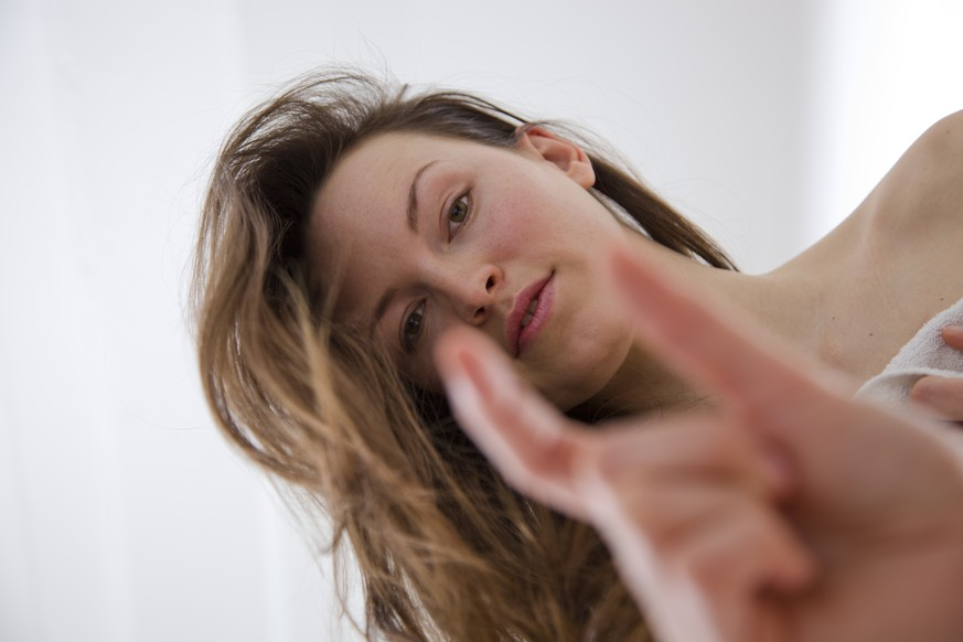 Low angle view of a young woman in a towel, looking down towards the camera, gesturing towards a man with a small penis. Horizontal shot.