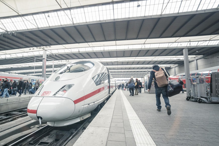 Munich, Germany - March 1, 2014: Intercity Express (ICE) trains at the central station in Munich. Passengers are on the way to boarding.