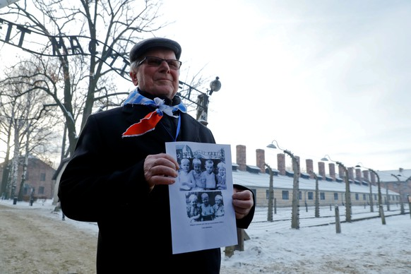 REFILE - CLARIFYING LOCATION  A survivor holds a poster at the former Nazi German concentration and extermination camp Auschwitz, as he attends ceremonies marking the 74th anniversary of the liberation of the camp and International Holocaust Victims Remembrance Day, in Oswiecim, Poland, January 27, 2019. REUTERS/Kacper Pempel
