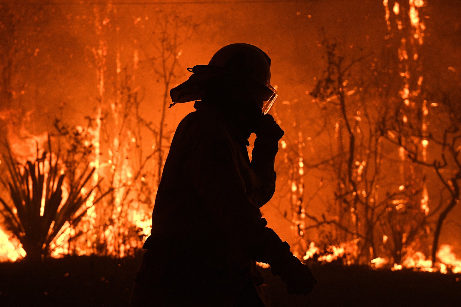 NSW Rural Fire Service crews protect properties on Waratah Road and Kelyknack Road as the Three Mile fire approaches Mangrove Mountain, Australia, December 5, 2019. Picture taken December 5, 2019.  AAP Image/Dan Himbrechts/via REUTERS    ATTENTION EDITORS - THIS IMAGE WAS PROVIDED BY A THIRD PARTY. NO RESALES. NO ARCHIVE. AUSTRALIA OUT. NEW ZEALAND OUT. NO COMMERCIAL OR EDITORIAL SALES IN NEW ZEALAND. NO COMMERCIAL OR EDITORIAL SALES IN AUSTRALIA.