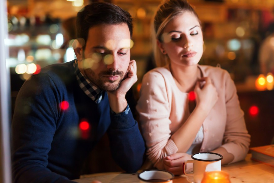 Sad couple having conflict and relationship problems sitting in bar