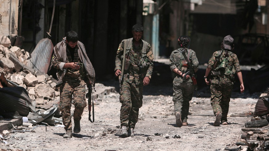 FILE PHOTO: Syria Democratic Forces (SDF) fighters walk on the rubble of damaged shops and buildings in the city of Manbij, in Aleppo Governorate, Syria, August 10, 2016. REUTERS/Rodi Said/File Photo