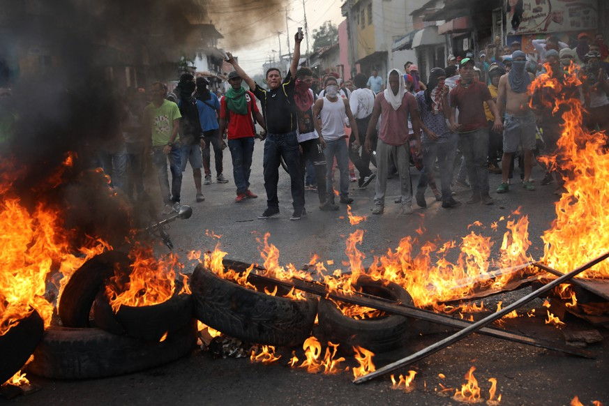 Demonstrators man a barricade during clashes with the Bolivarian National Guard in Urena, Venezuela, near the border with Colombia, Saturday, Feb. 23, 2019. Venezuela's National Guard fired tear gas on residents clearing a barricaded border bridge between Venezuela and Colombia on Saturday, heightening tensions over blocked humanitarian aid that opposition leader Juan Guaido has vowed to bring into the country over objections from President Nicolas Maduro. (AP Photo/Rodrigo Abd)