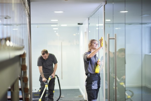 a female cleaning contractor is polishing the glass partition offices whilst In the background a male colleague steam cleans an office carpet in a empty office in between tenants.  .
