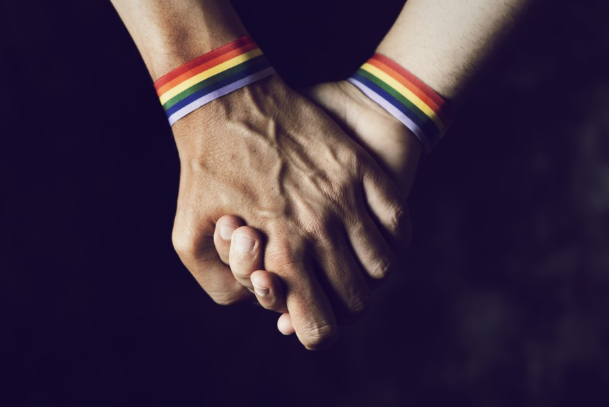 closeup of two caucasian men holding hands with a rainbow-patterned wristban on their wrists