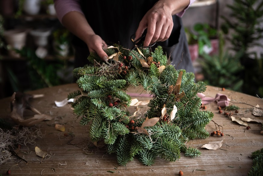 Woman making Christmas wreath of spruce, step by step. Concept of florist's work before the Christmas holidays.