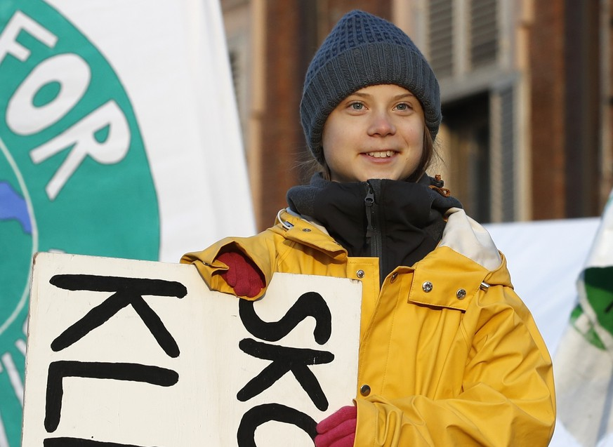 Swedish environmental activist Greta Thunberg holds a sign with writing reading in Swedish