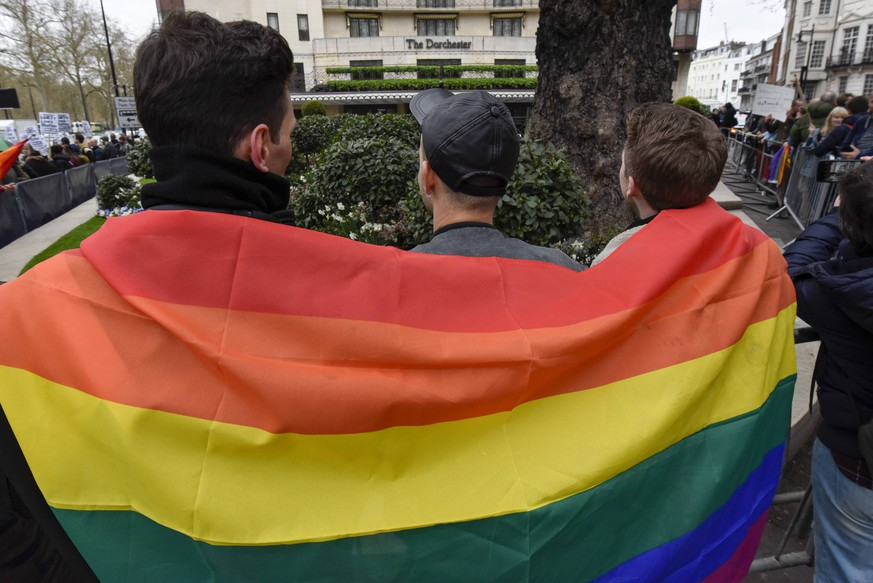 April 6, 2019 - London, UK - LONDON, UK. Members of the LGBT community wear a rainbow flag during a protest outside the Brunei-owned Dorchester Hotel in reaction to reports that the Sultan of Brunei decreed that adultery and gay sex is punishable by death by stoning in the Islamic sultanate. Several large clients of the Dorchester Hotel have already ceased bookings in response to the decree. London UK PUBLICATIONxINxGERxSUIxAUTxONLY - ZUMAl94_ 20190406_zaf_l94_032 Copyright: xStephenxChungx