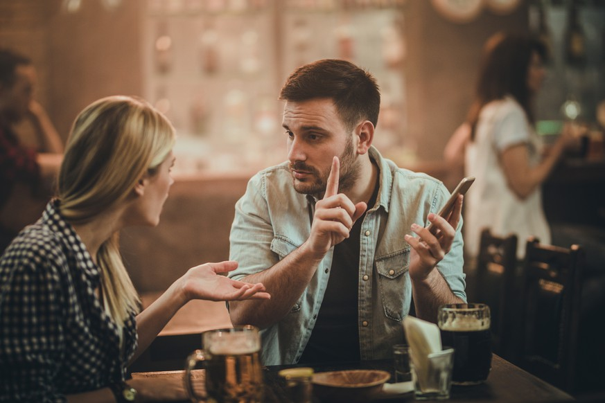 Young man using cell phone in a bar and arguing with his girlfriend.