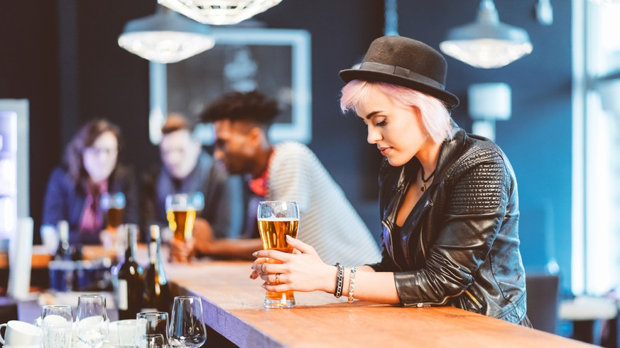 Cool blond young woman wearing leather jacet and hat drinking beer in the pub. Group of friends in the background.